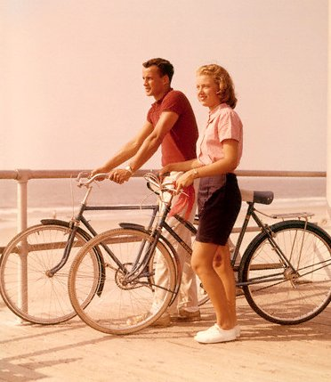 A couple with their bicycles on a sea side.