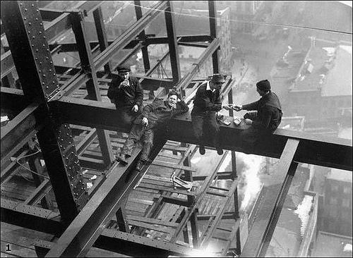 vintage men steelworkers resting on skyscraper beams