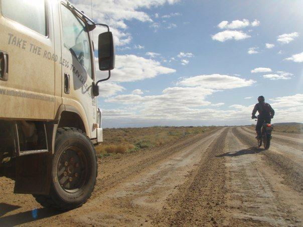 motorcyclist on dirt road next to van