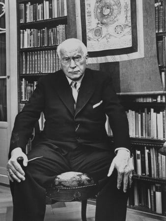 carl jung psychologist stern look sitting in chair in office