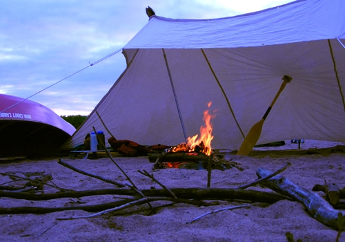 Lean to three sided tent camping shelter on beach with burning fire.