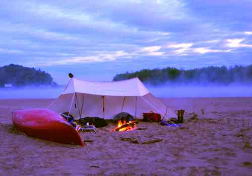 Lean to three sided tent camping shelter on beach with canoe.