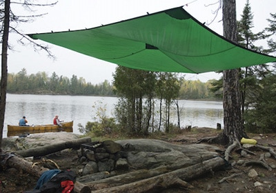 Tarp shelter strung high in trees campsite protection.