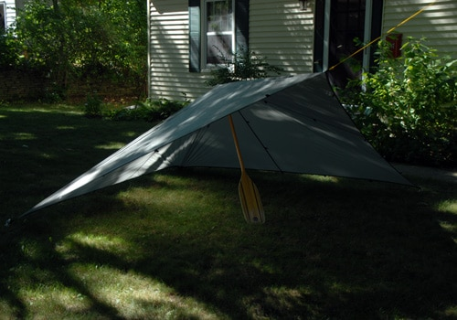Pitch a tarp with canoe paddle rope for quick shelter.