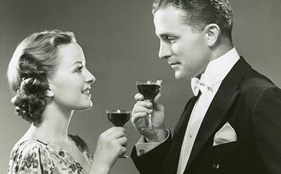 Vintage couple holding glasses of drink and looking at each other.