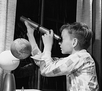 vintage young boy looking out window with telescope