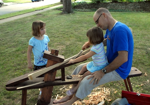 Kids helping in making of canoe paddle.