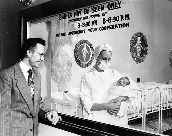 vintage man looking at newborn in infant ward hospital