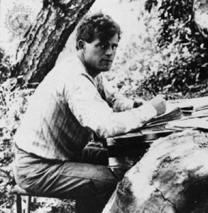 jack london writing outside at desk looking at camera
