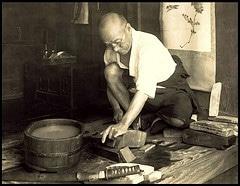 vintage older man in workshop sharpening tools