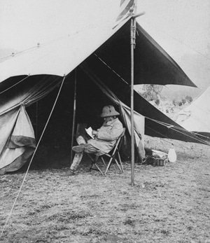 teddy theodore roosevelt sitting in tent reading