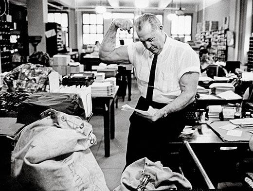 charles atlas older man in mail room flexing biceps