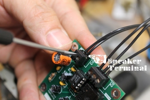 Connecting wires to an amp terminal.