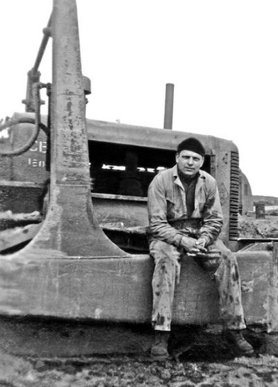 vintage man blue collar worker sitting on machinery