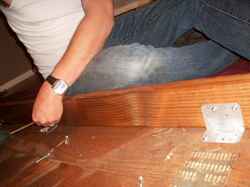 Man attaching brackets for screws on the table.