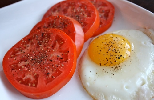 Fried egg with sliced tomatoes and pepper in the plate.