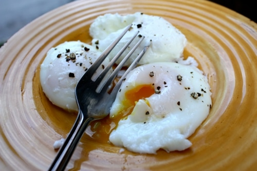 Poached eggs cracking in the plate with pepper and folk.