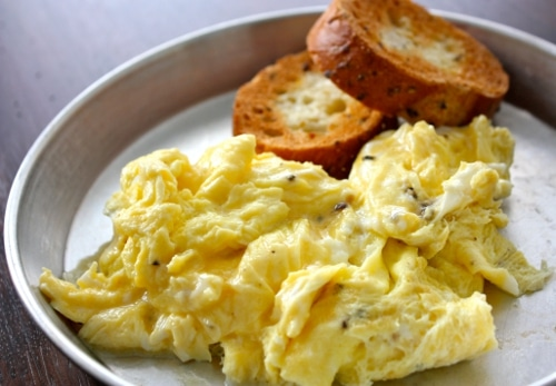 Scrambled eggs with wheat toast in tin plate.