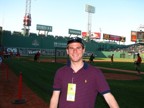 Man giving pose in front of baseball pitch.