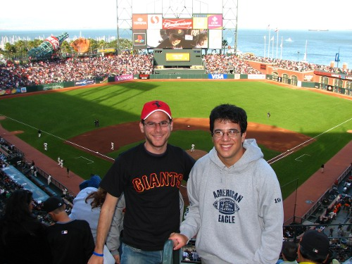 Two men posing at baseball stadium.