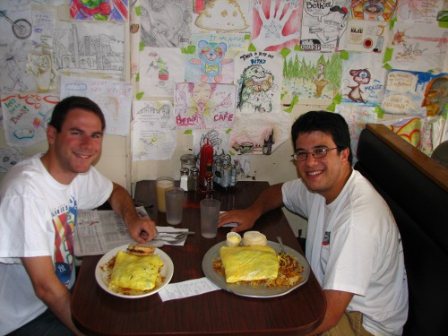 Men eating egg omlet in cafe.