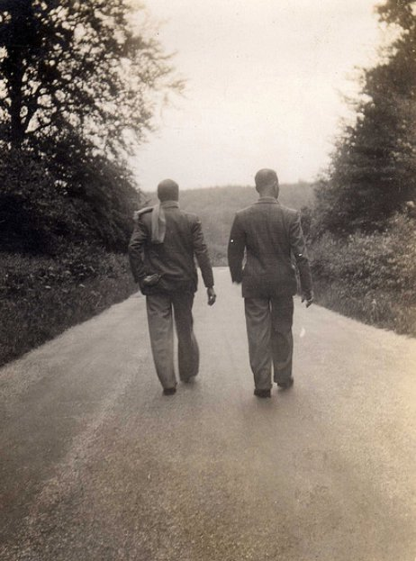 two men walking down middle of road backs to camera