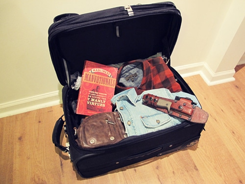 A knife holster in a suite case with a book.