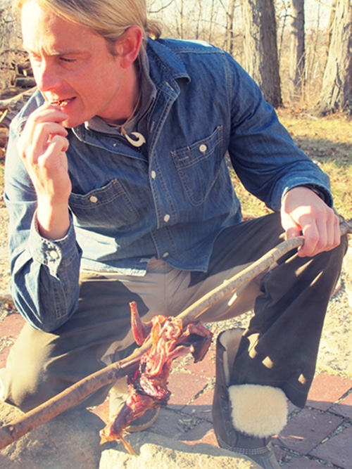 Man eating the cooked squirrel.
