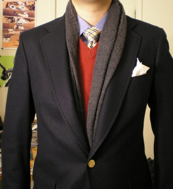 Man wearing scarf under suit coat layering with vest.
