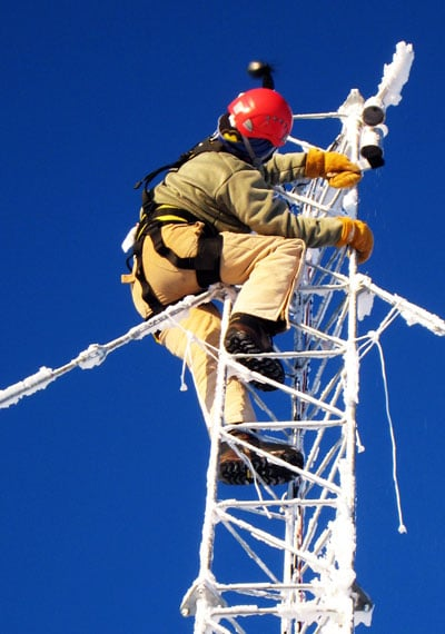 man working on tower covered in ice