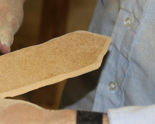 Sanding the side of the blade at an angle to look sharp.