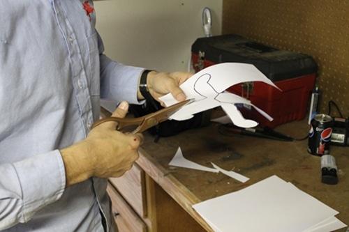 A man cutting a pattern with scissor.