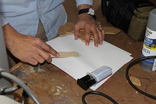 A man putting glue hilts Onto Main Sword.