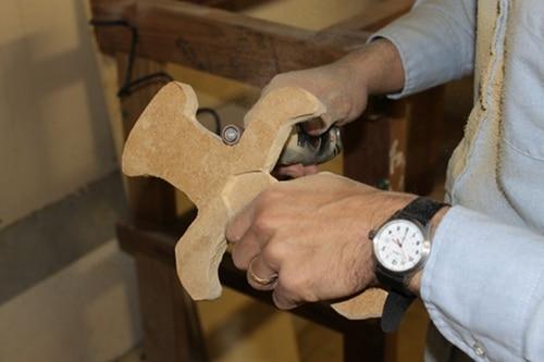 A man Sanding a wooden saw.