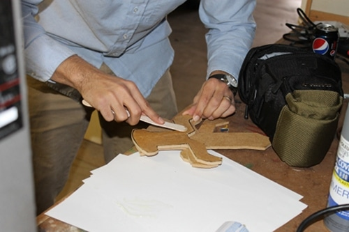 A man applying epoxy to the hilts and attaching them to the main sword.