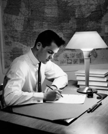 vintage young man studying at desk map on wall