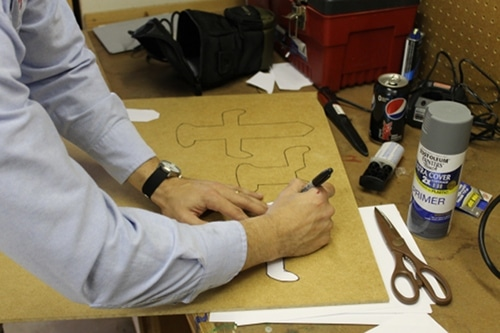 A man tracing two Sword hilts on the board.