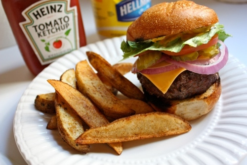 Bison burger with steak fries in paper plate with tomato ketchup.