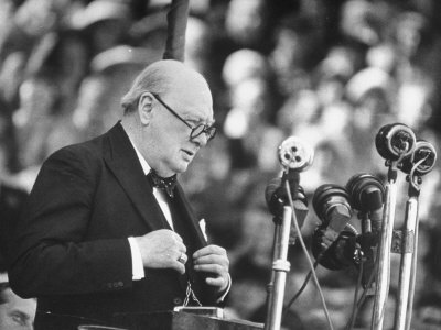 Winston Churchill giving speech glasses suit microphones.