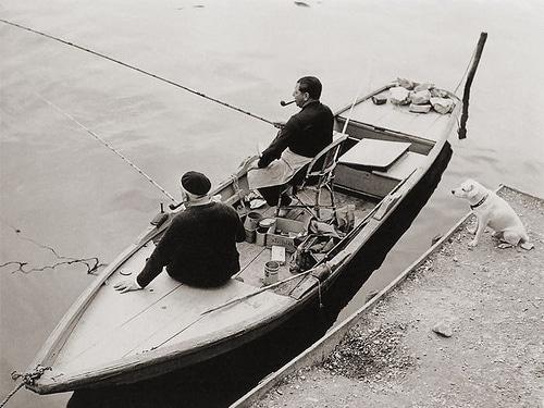 vintage men in fishing boat smoking pipes near dock