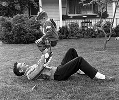 Vintage dad roughhousing with boy in the outside lawn.