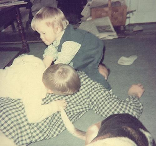 vintage dad roughhousing with 2 kids dog on floor