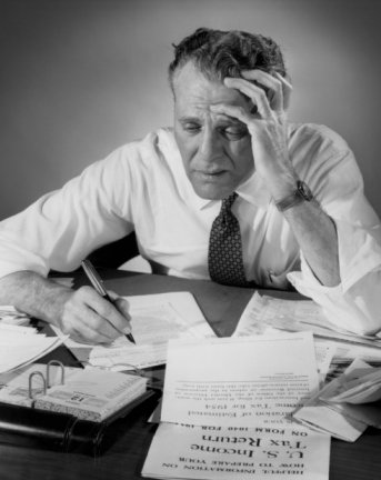 Vintage man looking stressed to see taxes papers.