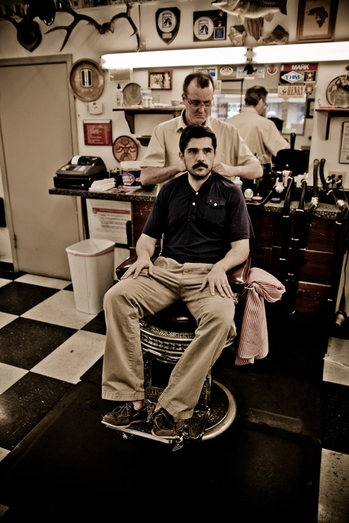 A man sitting at barbershop for hair cut.