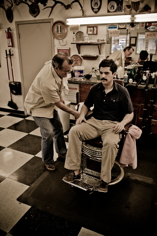 A man sitting on chair at barbershop.