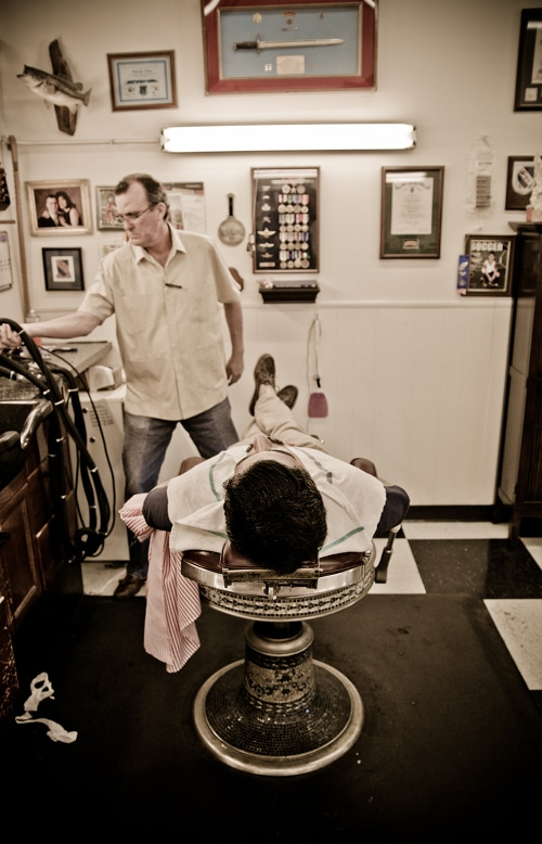 Man lying on the barber bench for shaving.