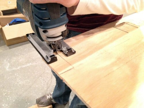 Cutting the edge corners of wood pieces using handsaw.
