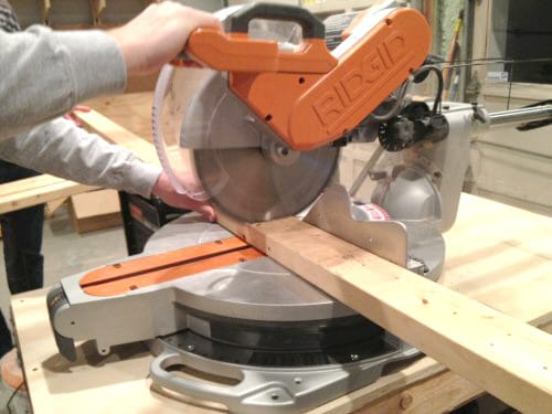 Man cutting wood piece with a miter saw.