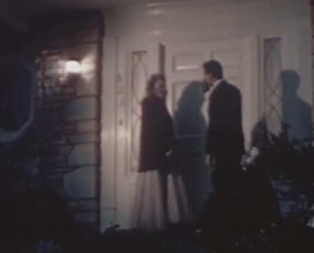 Vintage couple standing outside the door.