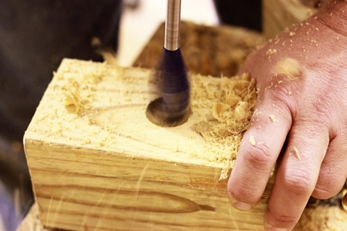 Man boring the holes in wooden piece.